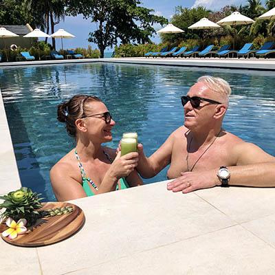 Happy, positive wellness resort guests drinking green juice.